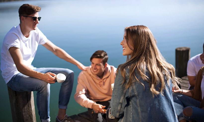 水辺に集まり話をする男女
