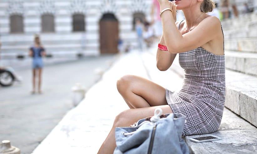 外で座って化粧をする女性