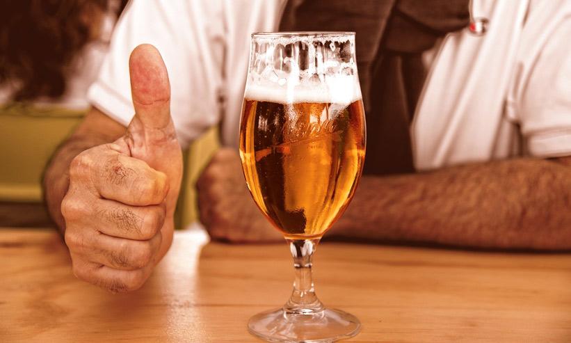 ビールの横でサムズアップをする男性