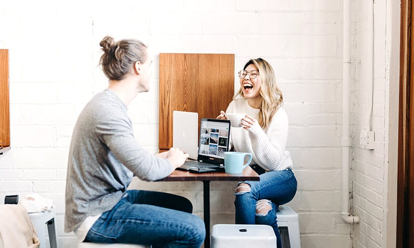カフェで笑いながら話しているカップル