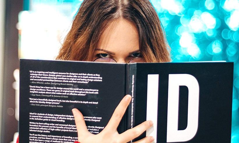 本で顔を隠しながら睨む女性