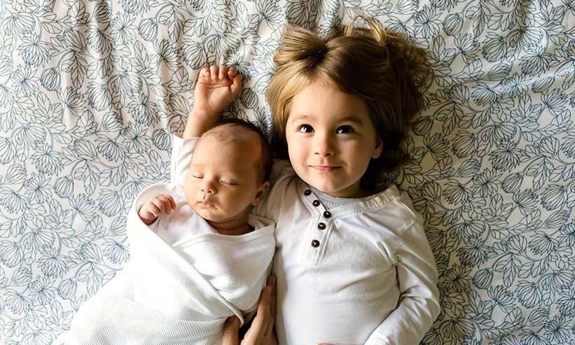 寝転がる赤ちゃんと女の子