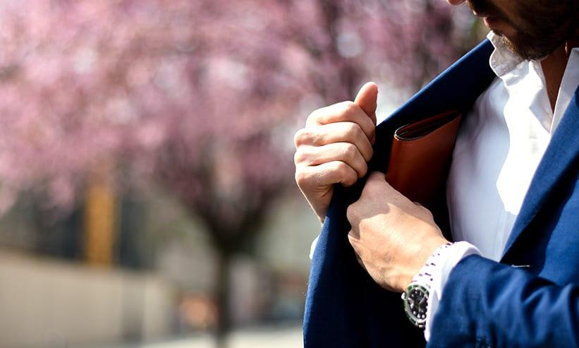 ジャケットの内ポケットから財布を出そうとする男性
