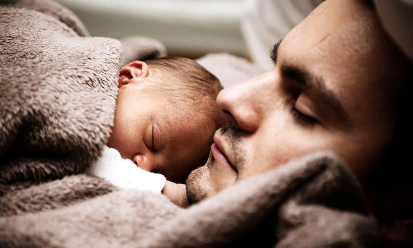赤ちゃんと一緒に眠る男性
