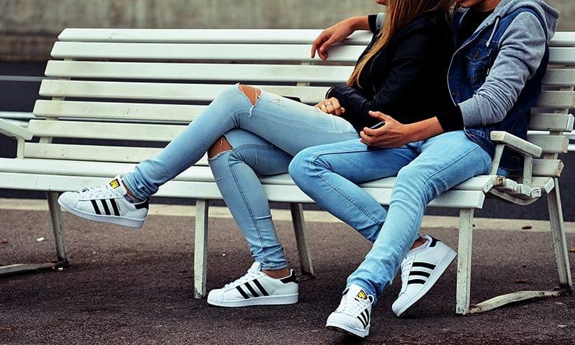 ベンチに寄り添って座るカップル