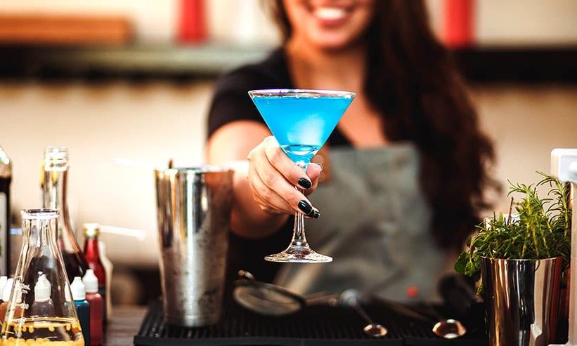 青いカクテルを差し出す女性のバーテンダー