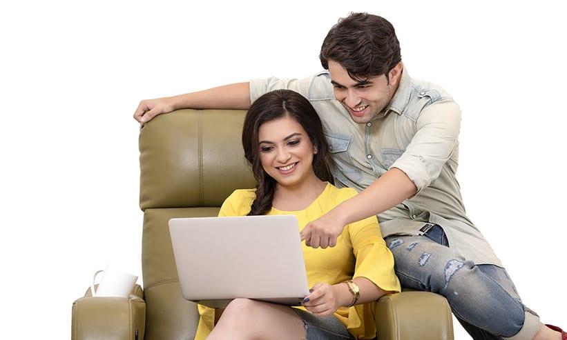 椅子に座りながらパソコンを見ているカップル