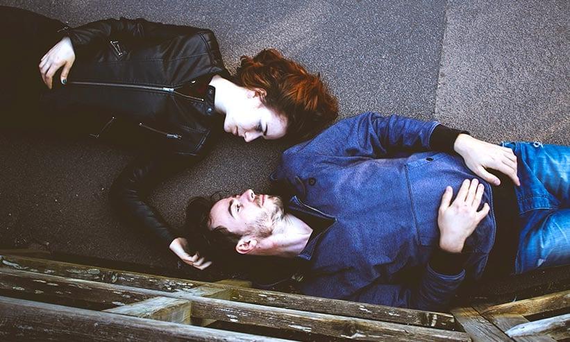 寝転がって見つめ合うカップル