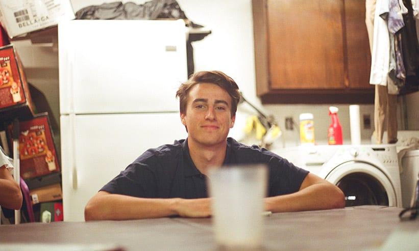 テーブルに置いた飲み物を見ている男性