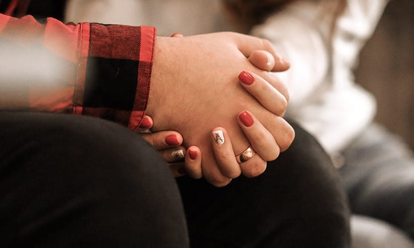 手を握り合っているカップル