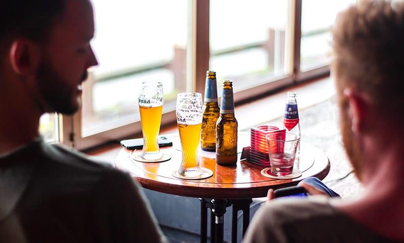 座ってビールを飲んでる2人の男性