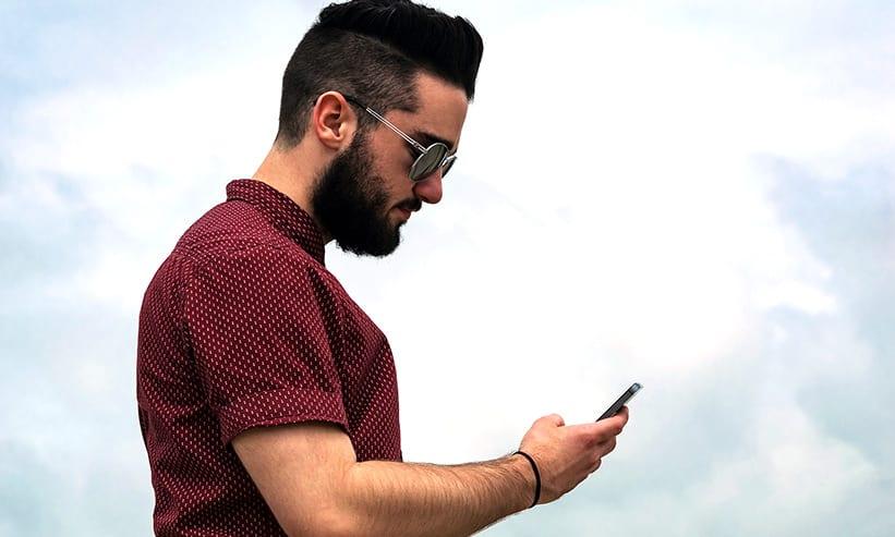 手に持ったスマートフォンを見つめる男性