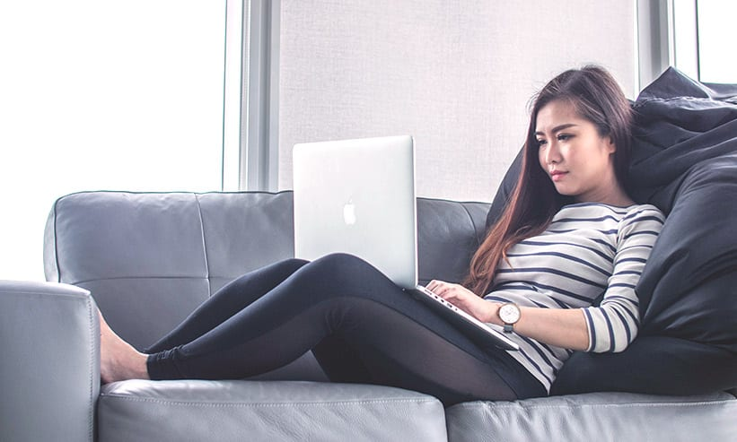 ソファーで足を伸ばしてPCを見ている女性