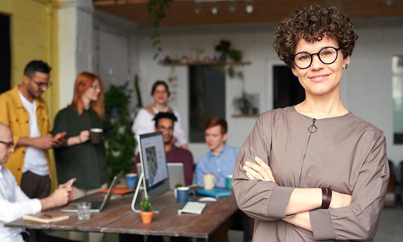 職場で腕組みをして立つ女性