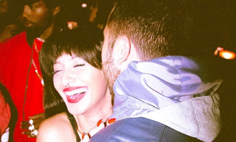 耳元で話す男性と笑っている女性