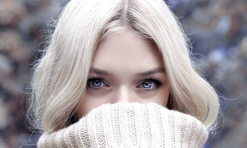 セーターで口元を隠した女性