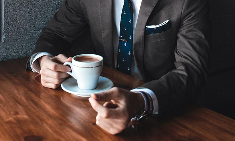 コーヒーを飲むスーツの男性