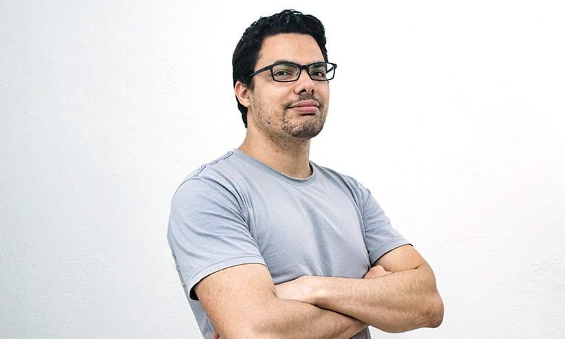 腕を組んでポーズを取るメガネの男性
