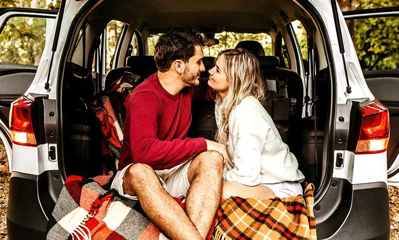 車のトランクで座って見つめ合うカップル