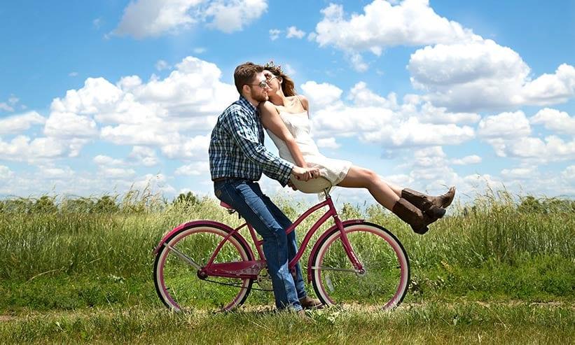 自転車に乗りながらキスをするカップル