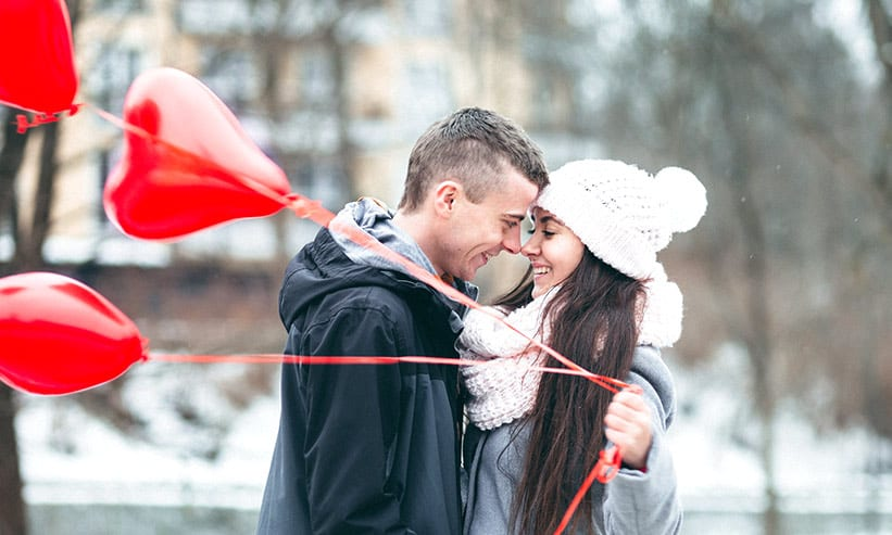 ハートの風船を持った女性に顔を近づける男性
