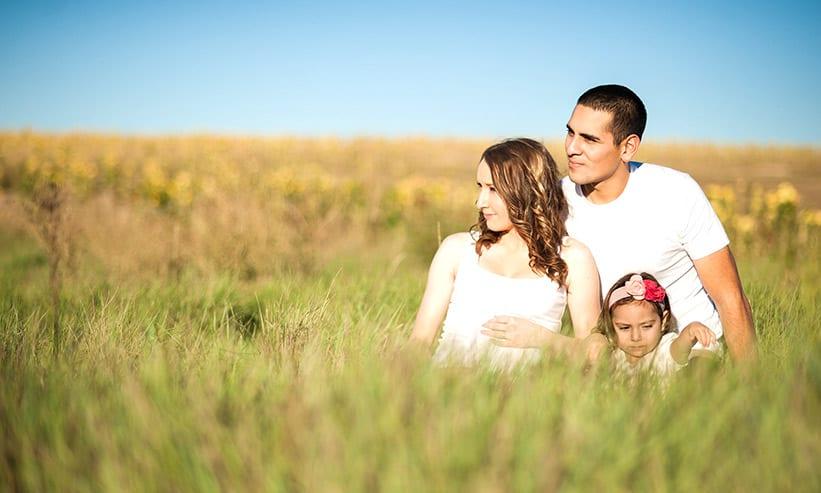 草原に座っている男女と女の子