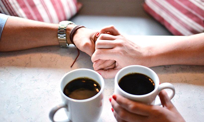カフェで手を取り合うカップル
