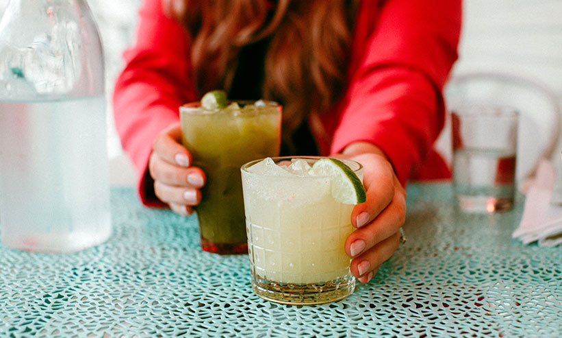 飲み物を両手に持ち片方を差し出す女性
