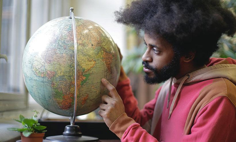 地球儀を人差し指で触っている男性