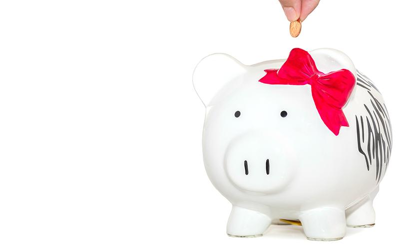 豚の貯金箱にお金を入れる様子