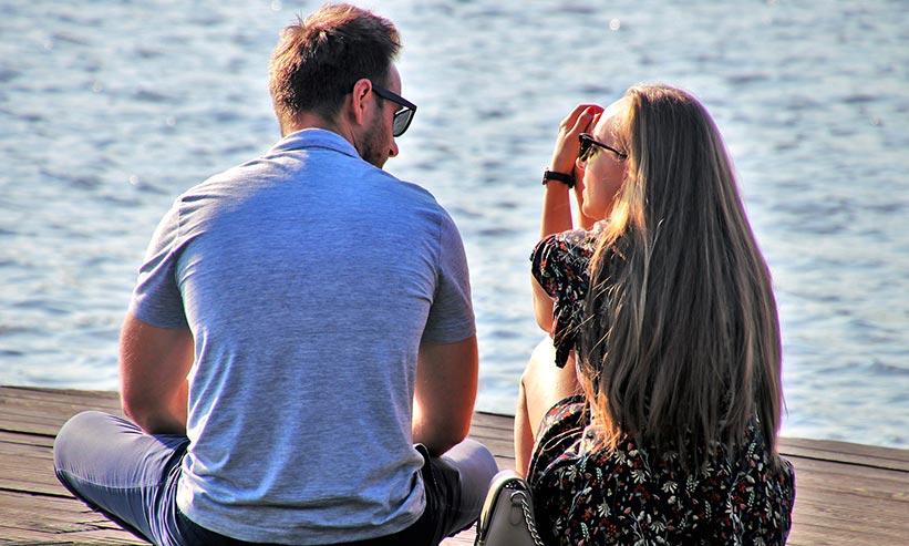 桟橋に座り話をするカップル