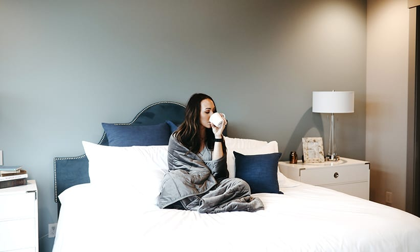 ベッドに座り毛布にくるまりながらコーヒーを飲む女性