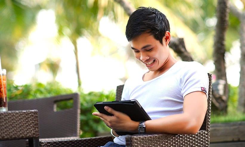 笑いながらタブレットを操作する男性