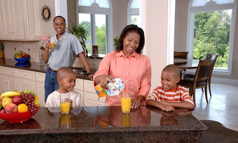 オレンジジュースを注いでいる女性とそれを見ている男性と2人の子供