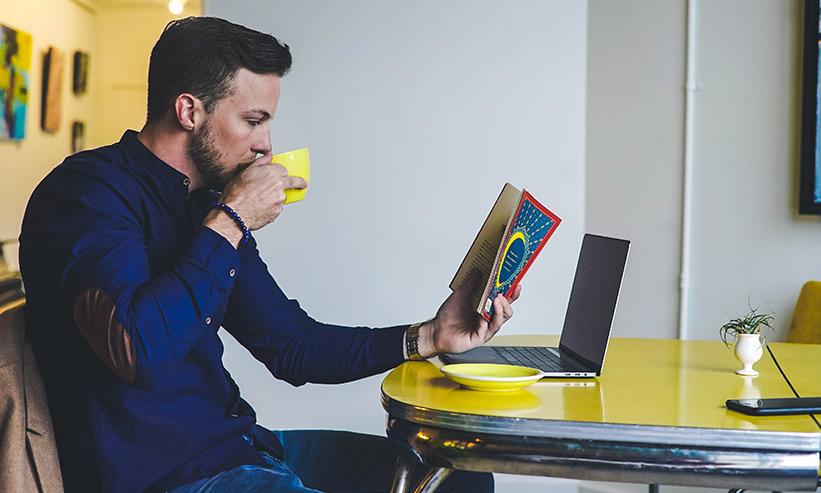 コーヒーを飲みながら本を見る男性