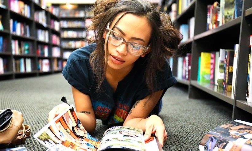 寝転んで漫画を読む女性