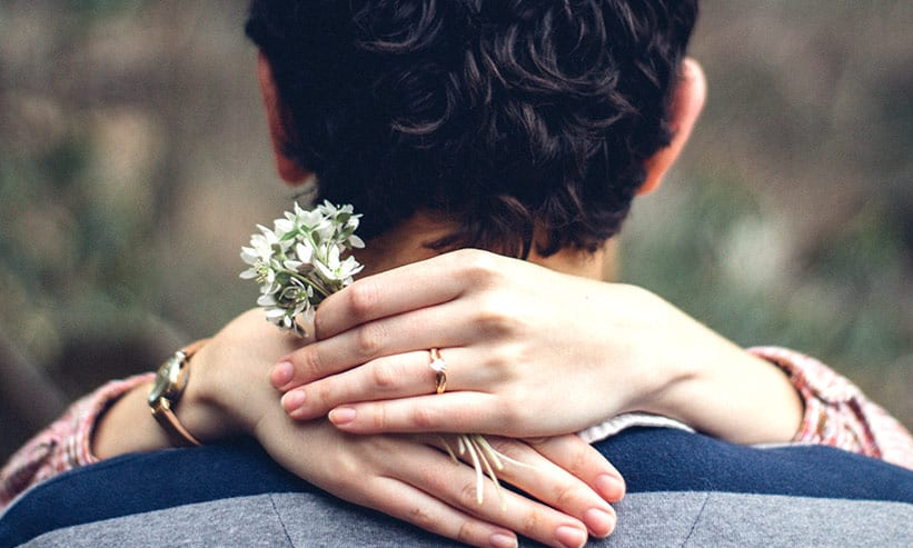 男性の肩に手を回す女性