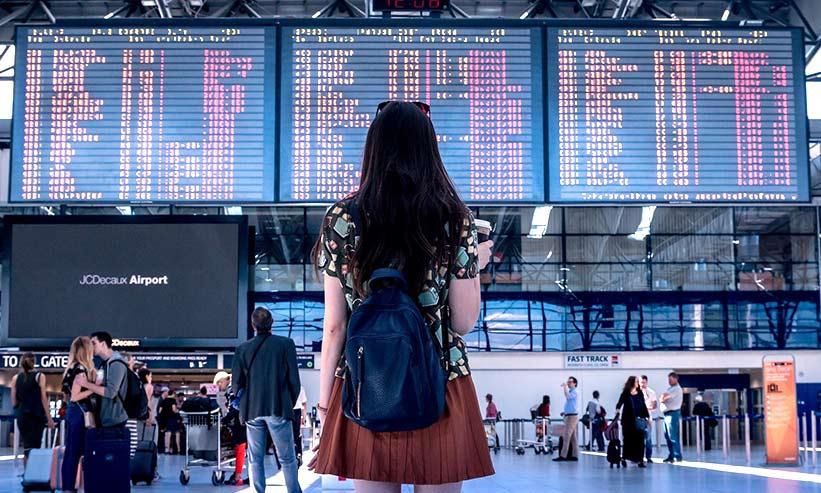 飛行機の案内表示盤を見る女性