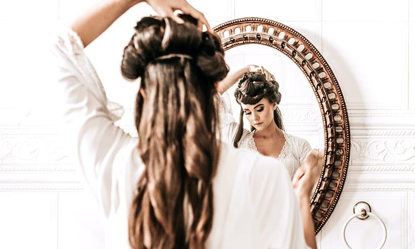鏡の前で髪を整えている女性