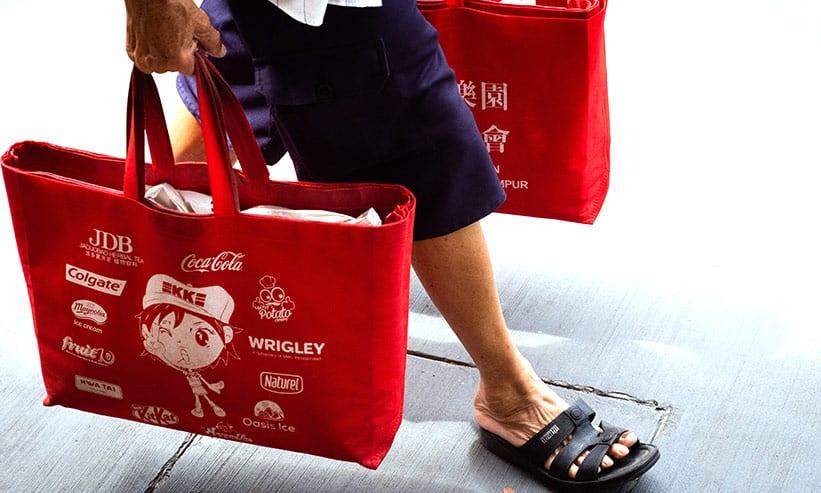 買い物バックを両手で持って歩く男性