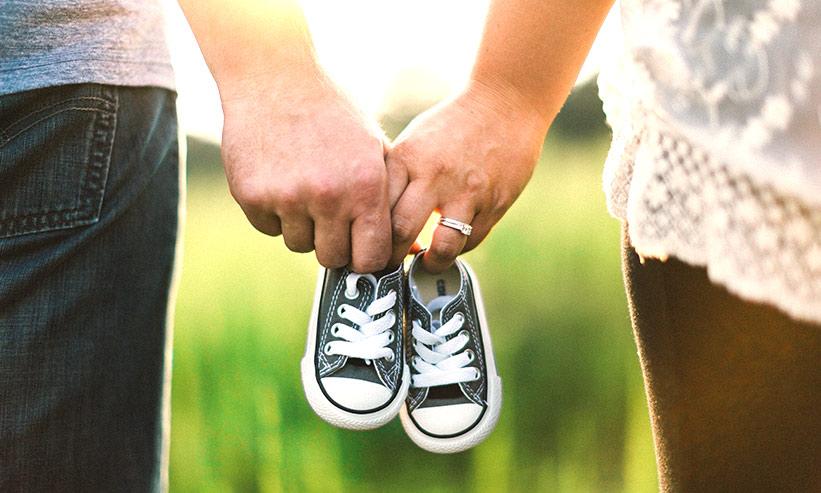 お互いに子供の靴を持つカップル