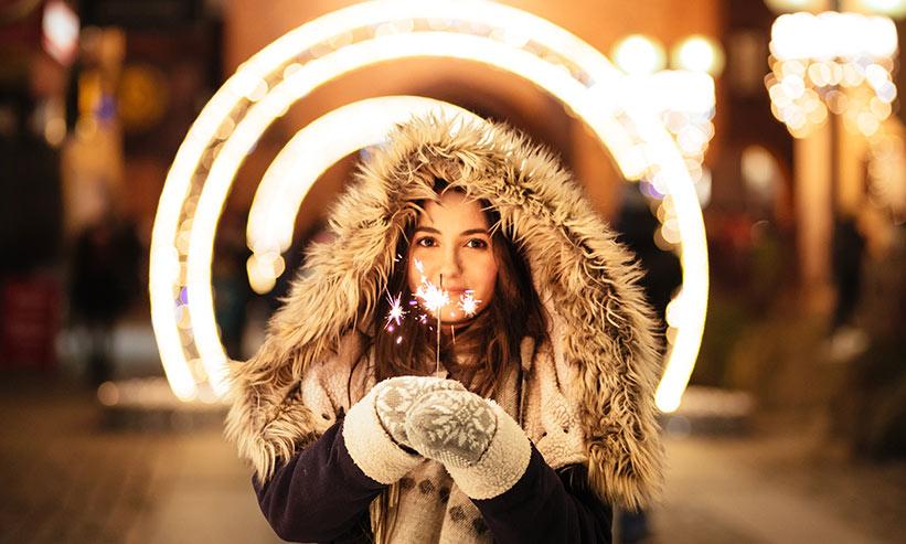 毛皮のフードを被り手に花火を持った女性