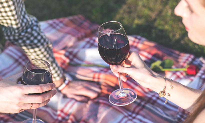 外でレジャーシートに座りワインで乾杯するカップル