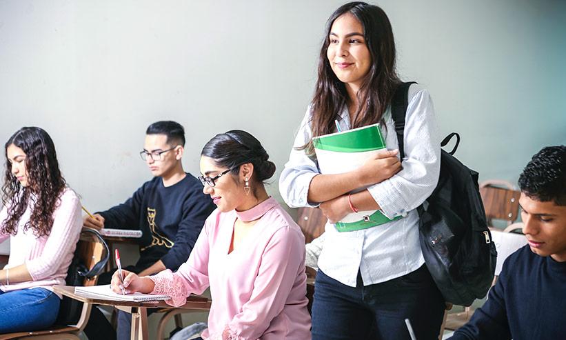 スクールの教室内で教科書を持って立っている女性
