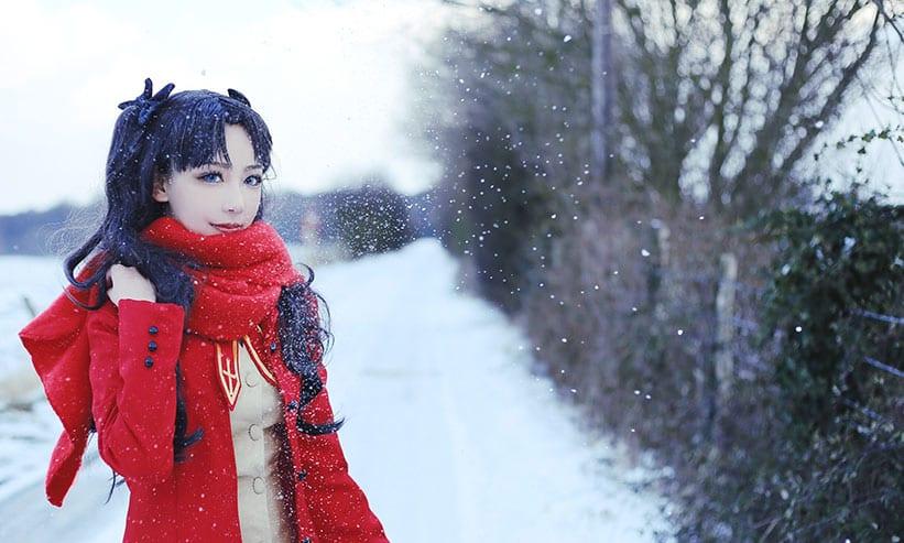 雪が降る中ポーズを取る赤いコートを着た女性