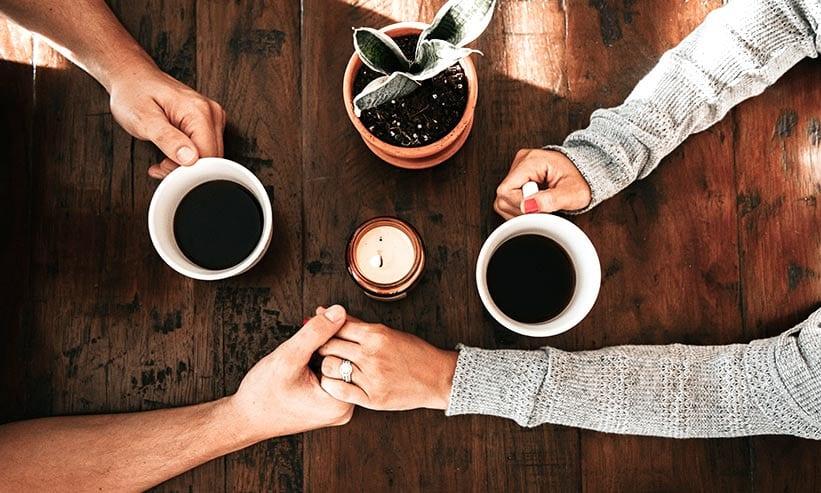 カフェでコーヒーを飲みながら手を繋ぐカップル