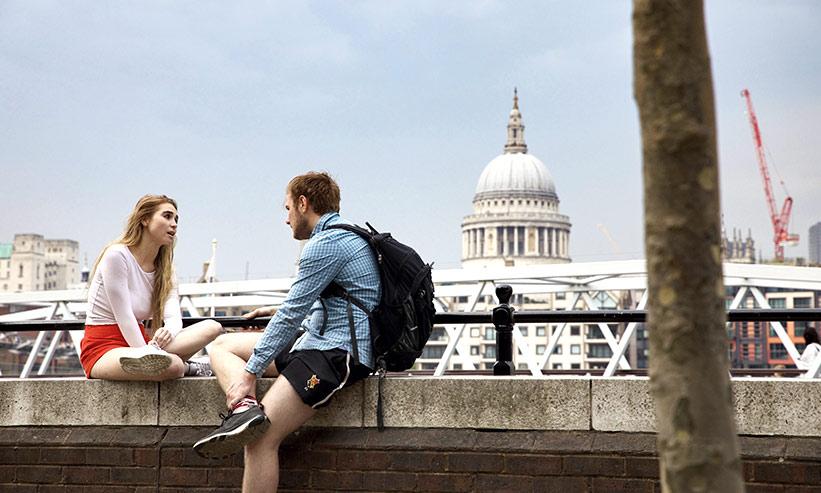 塀に座り話をするカップル