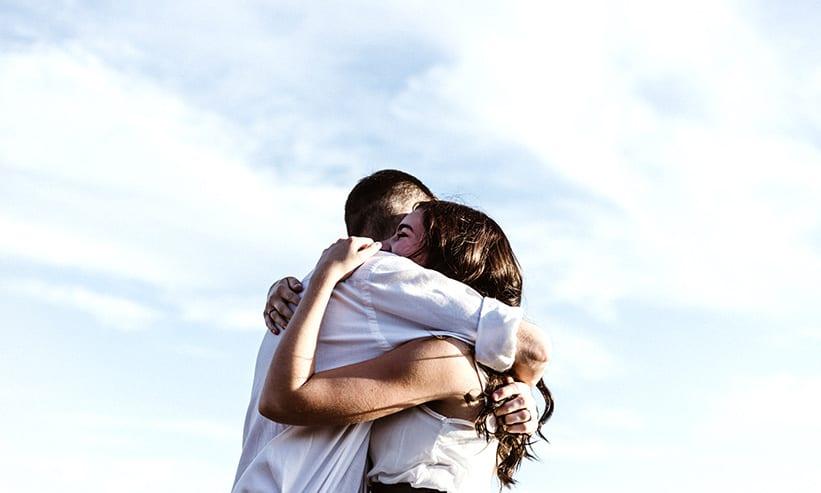 青空の下抱き合うカップル