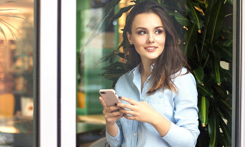 スマートフォンを持ち横を向く女性