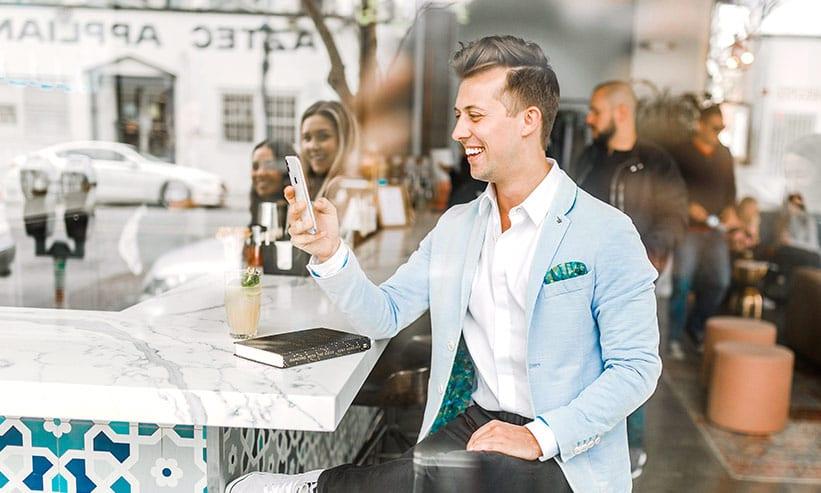 カフェでスマートフォンを操作する男性